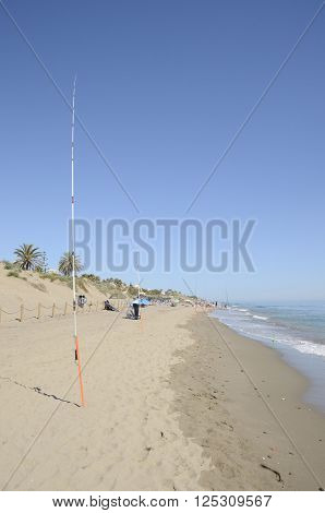 MARBELLA, SPAIN -APRIL 9, 2016: Row of fishing rods at the shore of the sea in Marbella Spain.