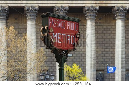 The Red Paris metro sign and Madeleine church in the background Paris France.