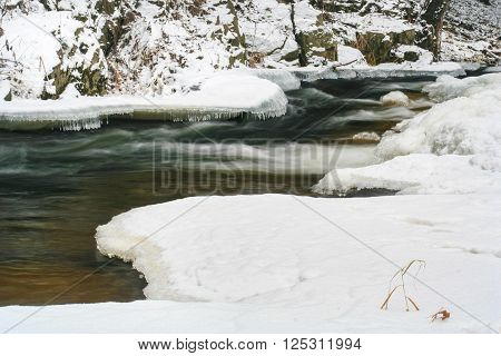 Meandering Frozen Creek in Winter with Ice in the Forest