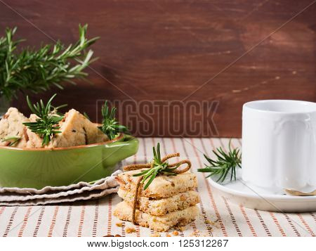 Butter cookies with rosemary, pignoli and pistachio nuts on table cloth with rosemary sprigs and a hot beverage in the background, copy space on dark wooden background
