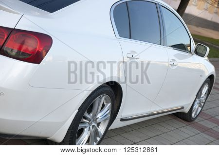 the white elegant car a sedan has stopped at the road