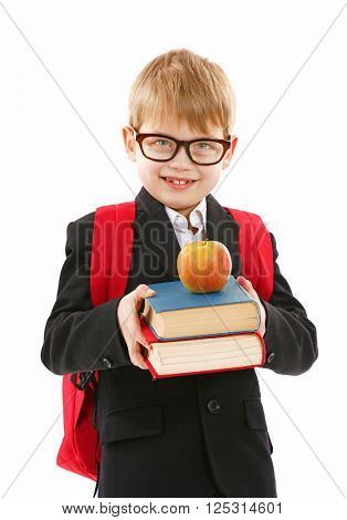 Schoolboy with backpack holding books and apple isolated on white