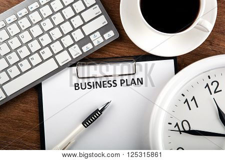 Document with title business plan and office supplies and clock