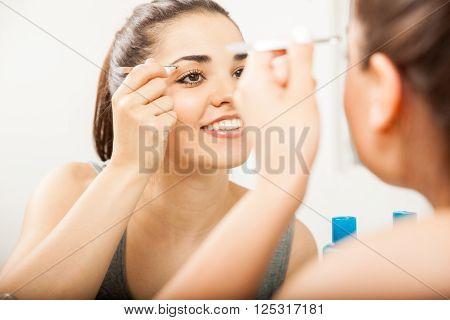Happy Girl Using Tweezers On Her Eyebrows