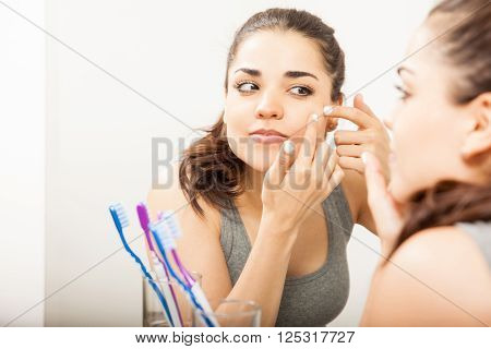 Cute Woman Looking At A Pimple