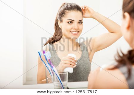 Reflection Of A Woman Putting On Deodorant