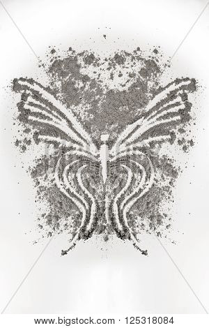 Butterfly design drawing in a pile of grey ash
