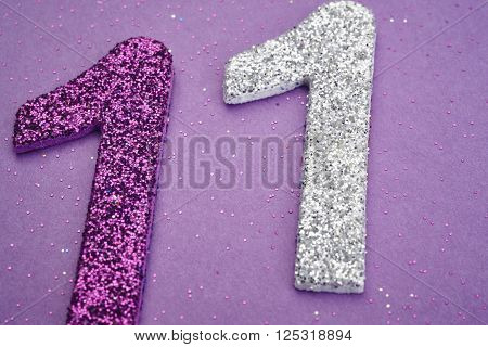 Number eleven purple silver color over a purple background. Anniversary. Horizontal