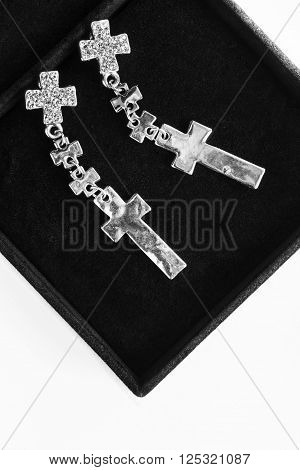 Silver cross earrings with crystals in black velvet box closeup