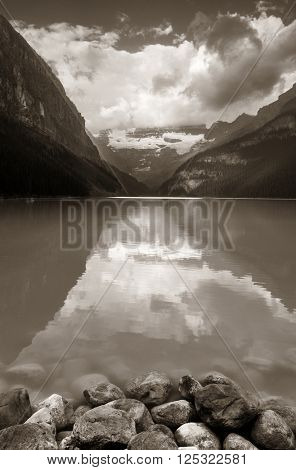 Lake Louise at sunrise with rocks in Banff national park with mountains and forest in Canada.