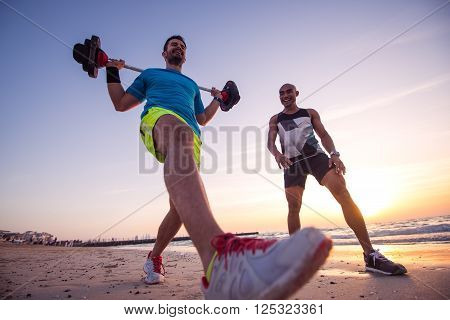Man exercising outdoors on the beach with personal trainer