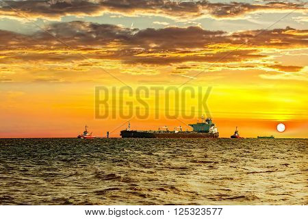 Tanker with escorting tugs at sea at sunset.