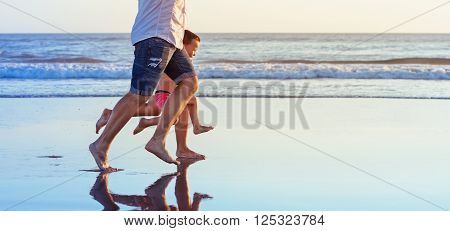 Barefoot legs in action. Happy family fun - parents with baby son running along edge of sea beach surf with sunset light. Active travel lifestyle water activity and game on summer vacation with child