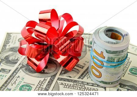 Roll stack of cash with red bow on banknotes  isolated. Money gift