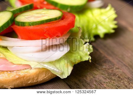 Sandwich with salad and other vegetables on old gray boards. On a half of a roll the lettuce leaf onions rings a tomato piece sausage lies. Close up small depth of sharpness