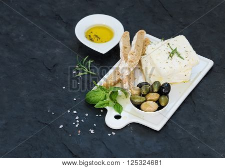 Fresh feta cheese with olives, basil, rosemary and bread slices on white ceramic serving board over black slate stone background, selective focus, copy space