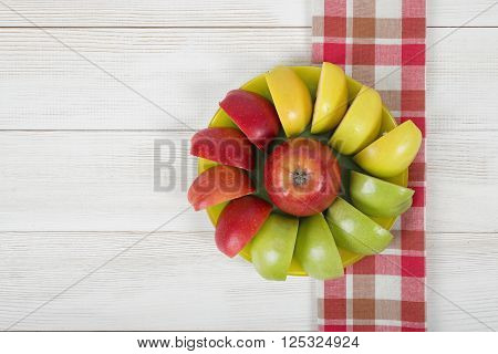 Yellow, green and red quartered apples laid out around the whole apple on a saucer. Table decoration.
