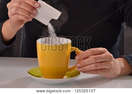 Pouring sugar bag on coffee cup.