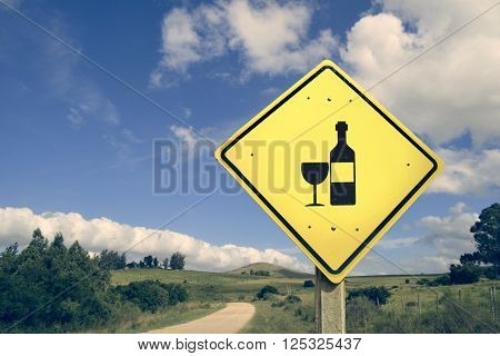 Wine bottle road sign on empty dirt street with vintage filter effect and nature landscape background.