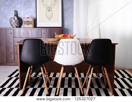 Room interior with commode, table and chairs