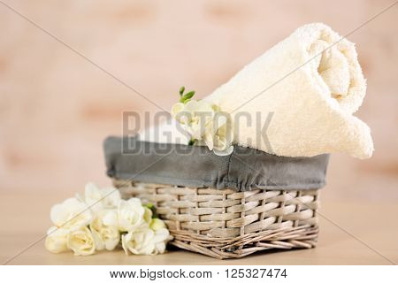 Towel and flowers in wicker basket