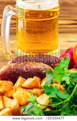 Grilled meat sausages with fried potatoes fresh produce and mug of beer on wooden board selective focus