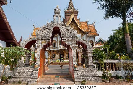 Carved gate to ancient Buddhist temple structure of Wat Buppharam in Chiang Mai Thailand. Historical importance temple was established in 1497 by King Muang Kaew