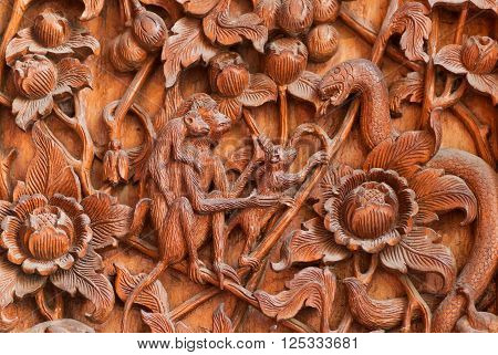 Monkeys are scared a snake - carved scene on wooden door of Buddhist temple in Chiang Mai Thailand.