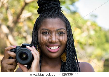Young Afro taking photos with a professional camera