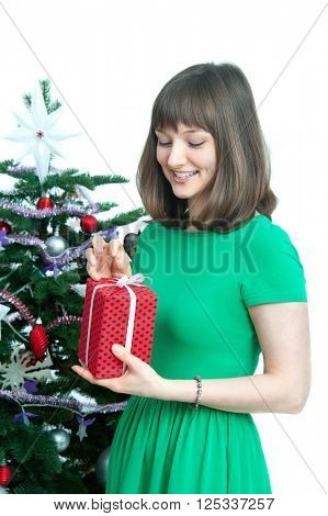 young  attractive woman with  red gift near christmas tree. isolated on white background
