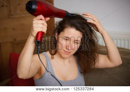 Young female dry her hair with red hair dryer