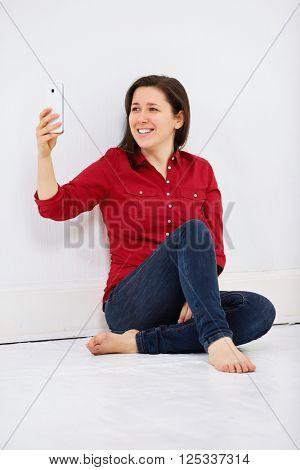 Joyful smiling woman taking selfie, sitting on white floor against white wall