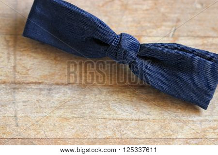 Vintage black silk tie against rustic wood table background