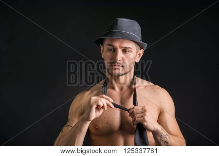 Handsome shirtless muscular man standing on dark background, wearing jeans, fedora hat and neck-tie on naked torso