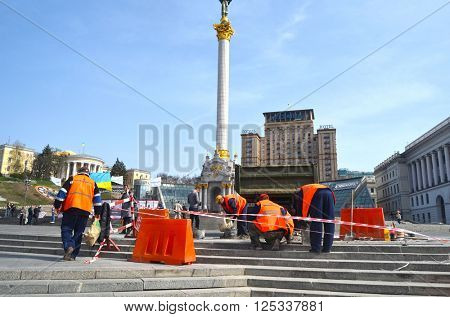 : Utility workers in orange vests repair after riot and vandalism 2013-2014. Khreshatik - central street of Kiev.At April 8,2016 in Kiev, Ukraine