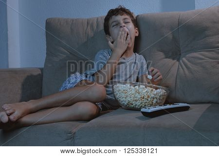 Small Boy Yawning On The Couch While Watching Tv And Eating Popcorn At Night In The Living Room