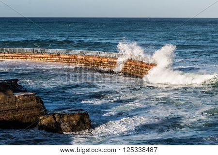 La Jolla Children's pool with nearby rocks and waves crashing over seawall.