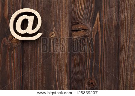 Wooden e-mail symbol on grunge wood background