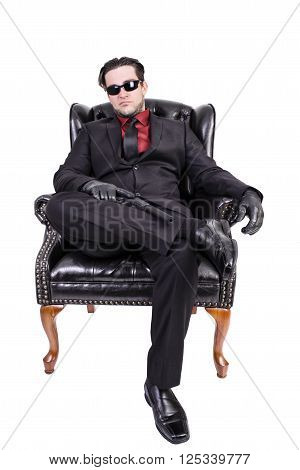 Handsome young man sitting on chair, ready to kill.