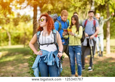 Young hiker woman with group of hikers in woods as hobby on a mission