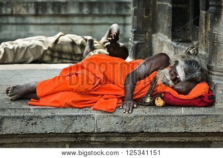 TIRUVANAMALLAI, INDIA - JANUARY 7, 2010: Sadhu -  religious ascetic or holy person - sleeping in Hindu temple Arunachaleswar. Tiruvanamallai, Tamil Nadu, India