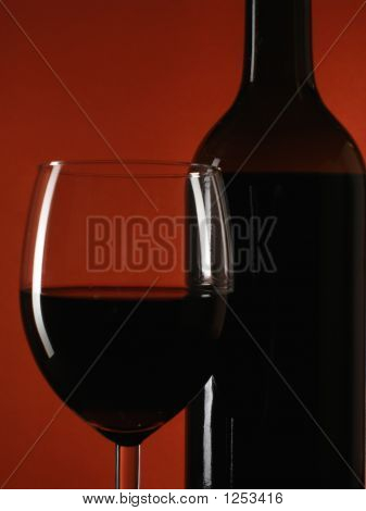 Bottle And Glass Over Deep Red
