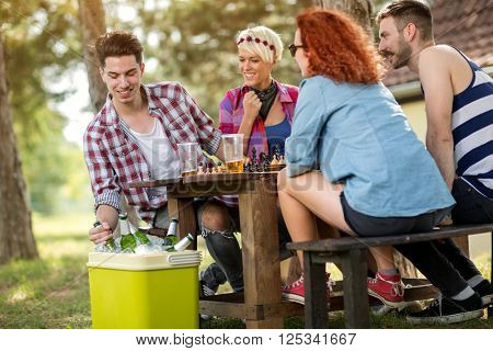 Cold beer refreshes youngsters while playing chess in woods