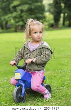 Girl playing in the park on a motorbike