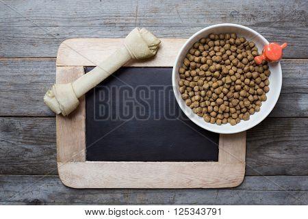Dog bone and dog food on wood table