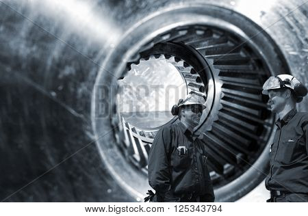 mechanics, workers in front of giant gears axle