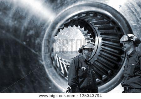 mechanics, workers in front of giant gears axle