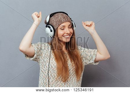 Smiling woman with closed eyes listening music in headphones and dancing over gray background