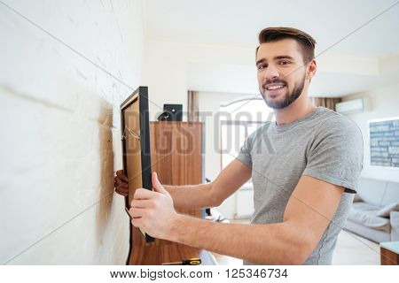Happy attractive young man hanging picture on the wall at home
