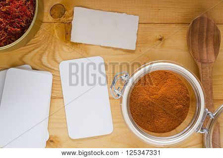 Strands of saffron and saffron powder on a wooden table